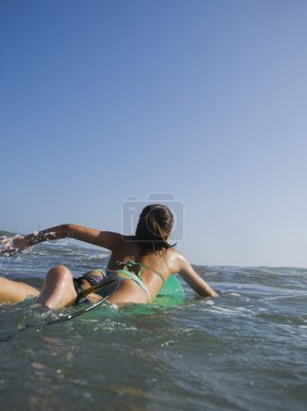 Hispanic girl paddling on surfboard