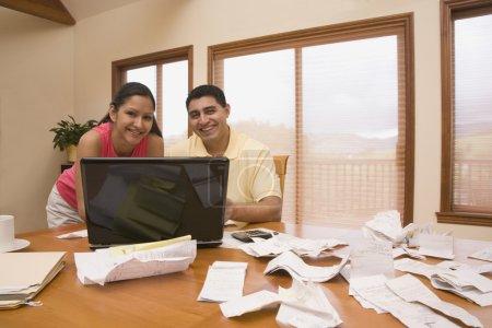 Hispanic couple paying bills