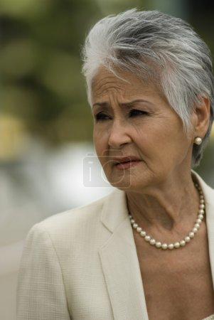 Senior Hispanic woman wearing pearls