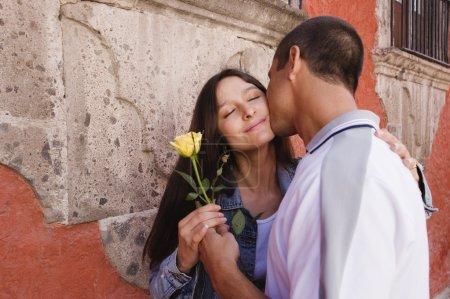 Hispanic couple kissing with rose
