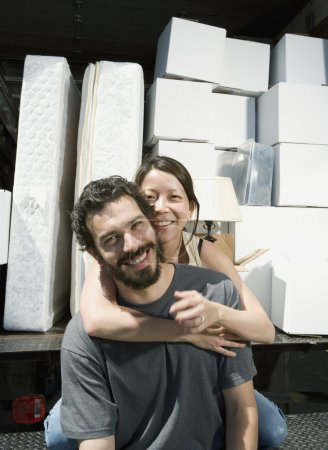 Multi-ethnic couple hugging on moving truck