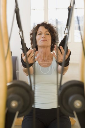 Senior woman stretching on exercise equipment