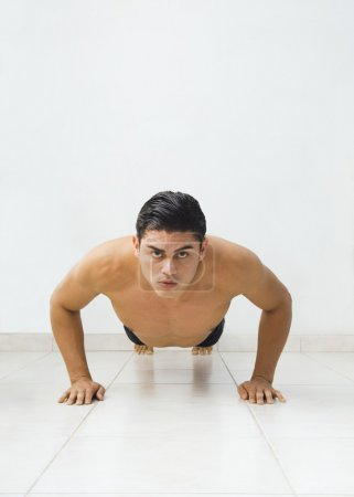 Bare-chested Hispanic man doing push-ups