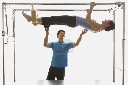 Instructor spotting woman on exercise equipment