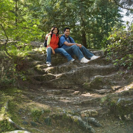 Indian couple sitting in woods