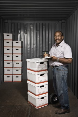 Senior African American male worker with stacks of boxes