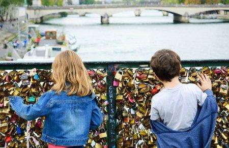Boy and girl on Love locks bridge in Paris.