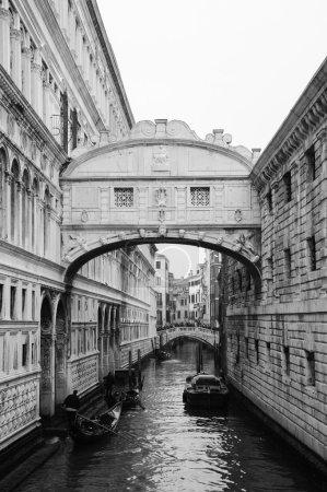 Gondolas floating on canal towards Bridge of Sighs