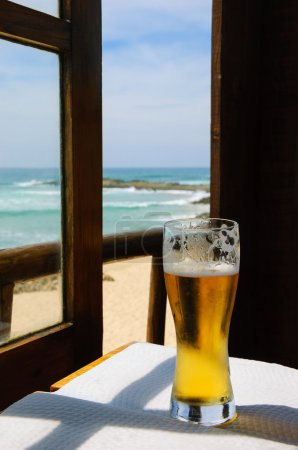 Cold beer on cafe terrace with the view on the ocean beach through the opened window. Algarve, Portugal. A game of light an shadow.