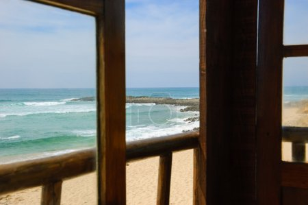 A view from the wooden terrace through the opened window on ocean beach. Algarve, Portugal. Selective focus on the landscape.