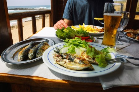 Traditional Portuguese lunch -  grilled sardines and chicken - at restaurant terrace with ocean beach view. Algarve, Portugal.