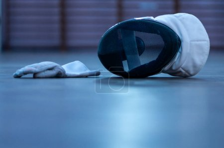 Photo for A fencing mask and a fencing glove on the floor - Royalty Free Image