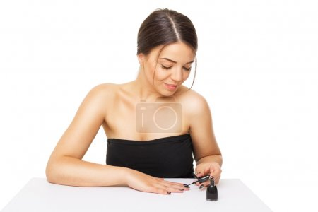 Beautiful young woman doing manicure at home