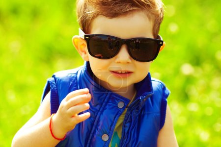 Eyewear concept. Stylish baby boy with ginger (red) hair in tren