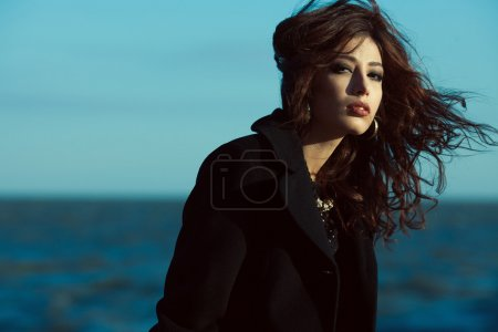 Photo for Emotive portrait of beautiful brunette with long curly hair in black coat. Luxurious golden accessories: earrings, necklace. Perfect make-up. Vogue style. Copy-space. Windy weather. Outdoor shot - Royalty Free Image