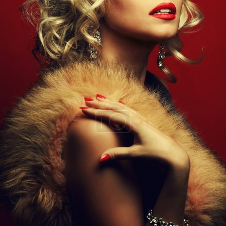 Rich woman concept. Portrait of beautiful blonde with furs