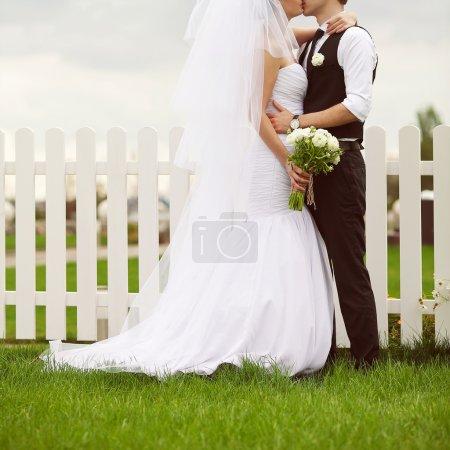 Photo pour Heureux couple marié jouant dans les bras et s'embrassant. Mariée tenant bouquet de mariage de fleurs beiges sur clôture en bois blanc et pelouse verte. Style country vintage. Plan extérieur - image libre de droit
