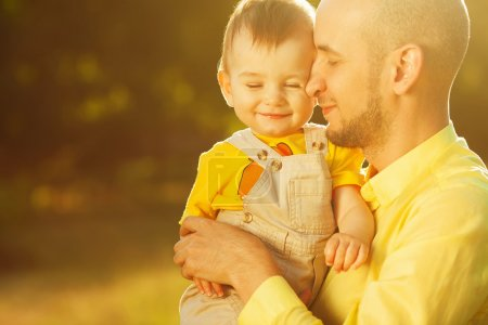 Photo for Happy family, friends forever concept. Smiling father and little son walking together in a park. Dad holding baby. Sunny summer day. Close up. Copy-space. Outdoor shot - Royalty Free Image