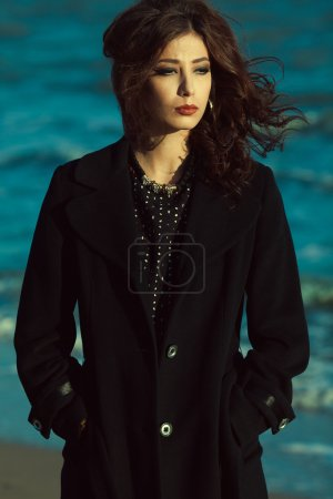 Photo for Bella donna concept. Beautiful brunette with long curly hair in black coat. Luxurious golden accessories: earrings, necklace. Perfect make-up. Street & Italian style. Windy weather. Outdoor shot - Royalty Free Image