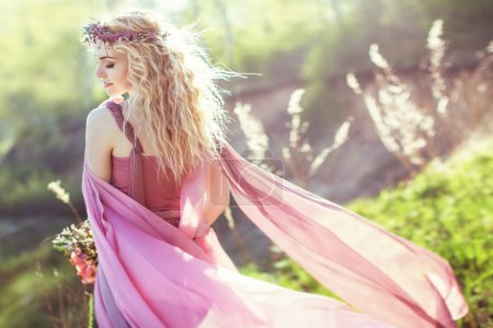 Belle fille blonde en robe longue rose sur fond de nature
