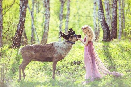 Photo pour Fille en robe de fée et rennes dans la forêt - image libre de droit