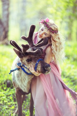 Portrait of Beautiful girl hugging a reindeer in the forest