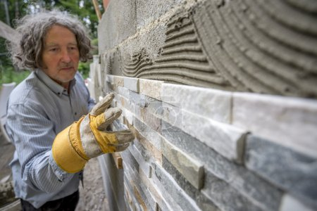 Older man placing an ornamental tile in to a glue