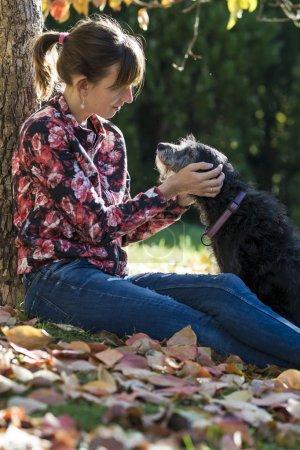 Woman sitting under a tree fondling her dog