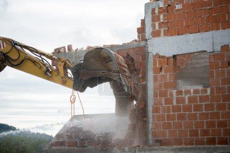 Backhoe demolishing a brick house