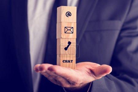 Photo pour Concept de communication d'entreprise en ligne avec un homme d'affaires détenant une pile de quatre cubes en bois en équilibre sur sa paume affichage d'icônes pour l'e-mail, une adresse web, mail, téléphone et chat. - image libre de droit
