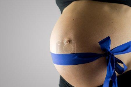 Pregnant woman wearing a blue ribbon