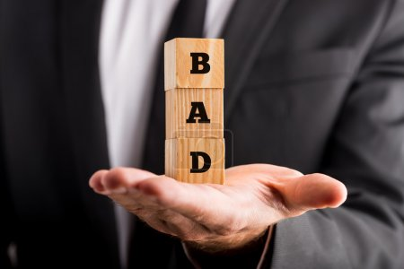 Photo for Businessman holding wooden alphabet blocks reading - Bad - balanced in the palm of his hand in a conceptual image, closeup view. - Royalty Free Image