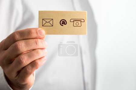 Photo pour Businessman Holding Small Card with Contact Icons. Over White Background. - image libre de droit