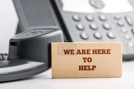 Photo pour Conception simple de concept de soutien à la clientèle Gros plan de la petite pièce en bois avec nous sommes là pour aider les textes au bureau de l'opérateur du service à la clientèle avec téléphone. - image libre de droit