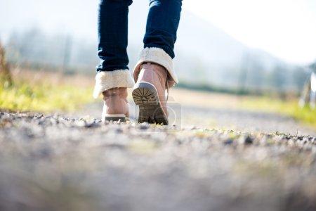 Femme qui marche le long d'un chemin rural