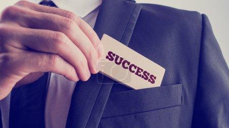Foto de Exitoso hombre de negocios mostrando una lectura de tarjeta de madera - Éxito - como él lo retira del bolsillo de su chaqueta de traje, de cerca de su mano con efecto de filtro retro descolorido. - Imagen libre de derechos