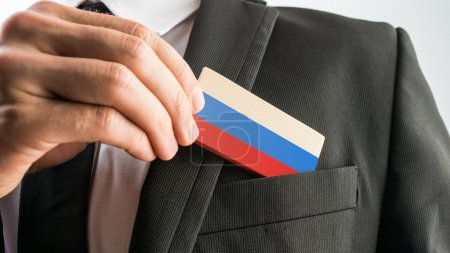 Photo for Man withdrawing a wooden card painted as the Russian flag from his suit pocket, close up of his hand. - Royalty Free Image