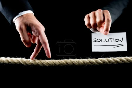 Photo for Metaphoric image of male hand walking on frayed rope towards solution. - Royalty Free Image