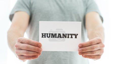 Photo pour Gros plan d'un homme tenant une carte blanche avec le signe Humanité dessus . - image libre de droit