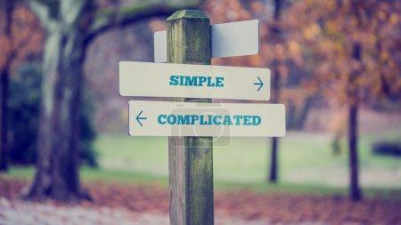 Photo pour Panneau rustique en bois dans un parc d'automne avec les mots Simple - Complexe offrant un choix d'action et d'attitude avec des flèches pointant dans des directions opposées dans une image conceptuelle . - image libre de droit