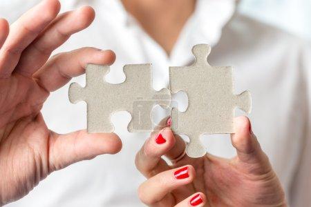 Foto de Concepto trabajo en equipo de dos piezas del rompecabezas están encajadas entre sí de mano masculina y femenina en un concepto de desafío, intercambio de ideas y solución de. - Imagen libre de derechos
