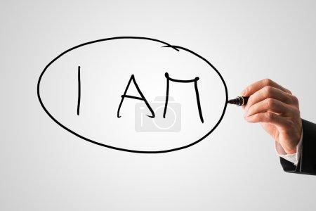 Photo pour Gros plan d'une main de thérapeute écrivant des lettres Je suis sur un écran virtuel gris. Concept d'essence personnelle, de conscience de soi et de soutien mental . - image libre de droit