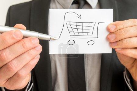 Photo pour Concept d'achats et d'achats avec un homme d'affaires tenant un croquis dessiné à la main d'un panier avec une flèche d'entrée à la main avec un stylo, vue rapprochée de la carte . - image libre de droit