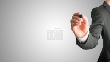 Photo for Closeup of male hand holding a black marker about to write something on a graduated grey background with central highlight and plenty of copyspace for your text. - Royalty Free Image