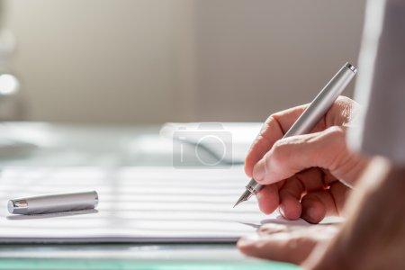 Photo pour Vue devant le bras d'un collègue d'un homme d'affaires écrivant sur un document avec un stylo plume, gros plan sur la main . - image libre de droit