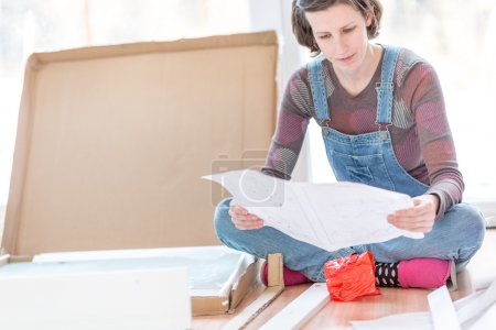 Photo pour Young woman in dungarees sitting on the floor reading instructions on how to assemble recently delivered flat pack furniture. - image libre de droit