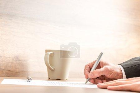 Photo pour Mains d'un homme d'affaires écrivant avec un stylo argenté sur une feuille de papier, à un bureau en bois, à côté d'une tasse de café ou de cappuccino, avec un espace de copie sur un mur beige flou . - image libre de droit