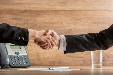 Handshake of business  partners above a written agreement