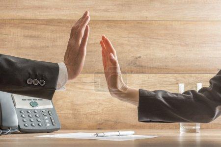 Photo pour Deux mains atteignent salut-cinq à travers la table d'affaires afin de célébrer une affaire réussie, bras en costumes noirs, téléphone, document avec stylo et verre d'eau visible, fond en bois . - image libre de droit