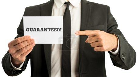 Photo pour Plan rapproché de l'homme d'affaires ou du vendeur pointant vers une carte blanche avec un signe garanti là-dessus. Conceptuel du marketing d'entreprise et du commerce de qualité. - image libre de droit